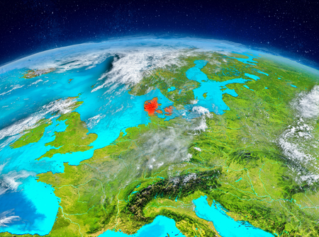 Orbit view of Denmark highlighted in red on planet Earth with highly detailed surface textures. 3D illustration.