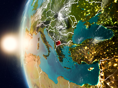 Satellite view of Macedonia highlighted in red on planet Earth with clouds and visible country borders during sunset. 3D illustration.