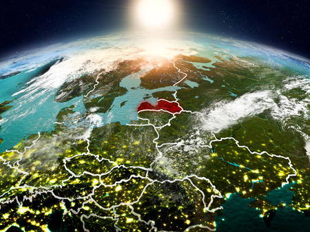 Sunrise above Latvia highlighted in red on model of planet Earth in space with visible country borders. 3D illustration. Stock Photo