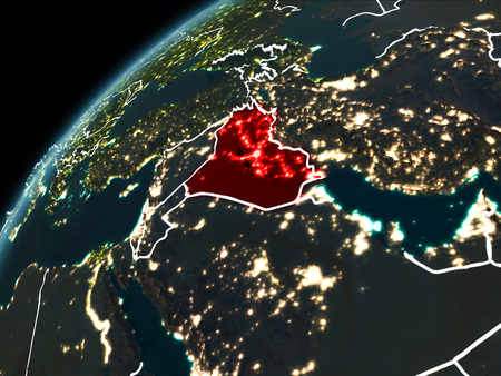 Iraq in red on planet Earth at night with visible borderlines and city lights. 3D illustration.