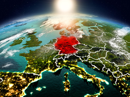 Sunrise above Germany highlighted in red on model of planet Earth in space with visible country borders. 3D illustration. Stock Photo