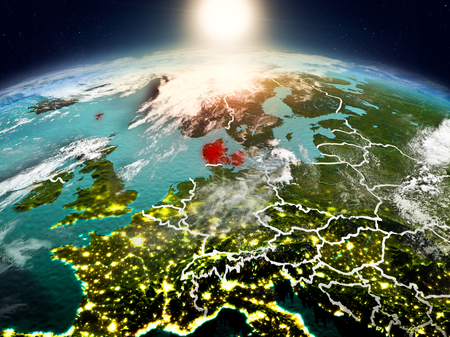 Sunrise above Denmark highlighted in red on model of planet Earth in space with visible country borders. 3D illustration. Stock Photo