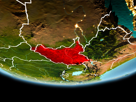 Country of South Sudan in red on planet Earth in the evening with visible border lines and city lights. 3D illustration.