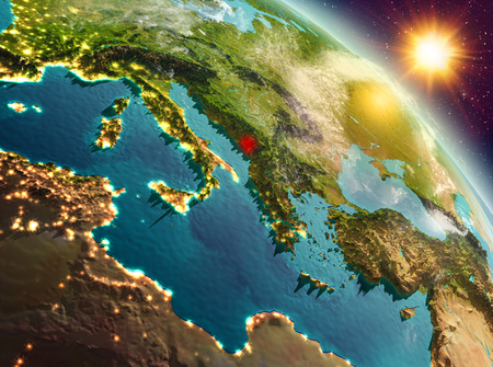 Sunrise above Montenegro highlighted in red on model of planet Earth in space. 3D illustration.
