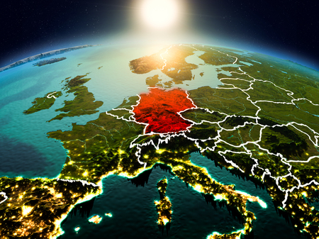 Sunrise above Germany highlighted in red on model of planet Earth in space with visible country borders. 3D illustration. Reklamní fotografie