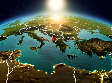 Sunrise above Albania highlighted in red on model of planet Earth in space with visible country borders. 3D illustration.