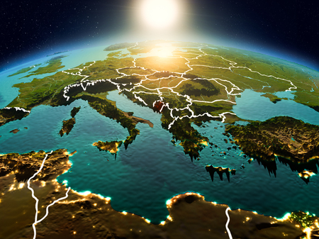 Sunrise above Montenegro highlighted in red on model of planet Earth in space with visible country borders. 3D illustration. Stock Photo