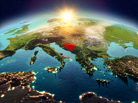 Satellite view of Bosnia and Herzegovina highlighted in red on planet Earth with clouds during sunrise. 3D illustration.
