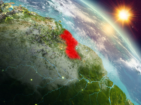 Sunrise above Guyana highlighted in red on model of planet Earth in space. 3D illustration. Stock Photo