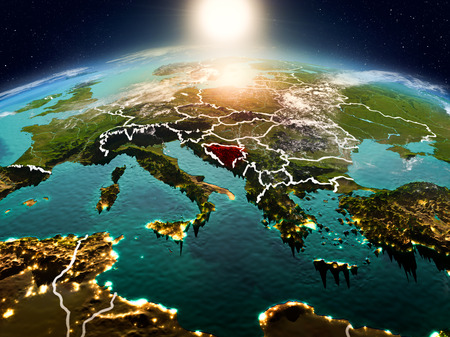 Sunrise above Bosnia and Herzegovina highlighted in red on model of planet Earth in space with visible country borders. 3D illustration.