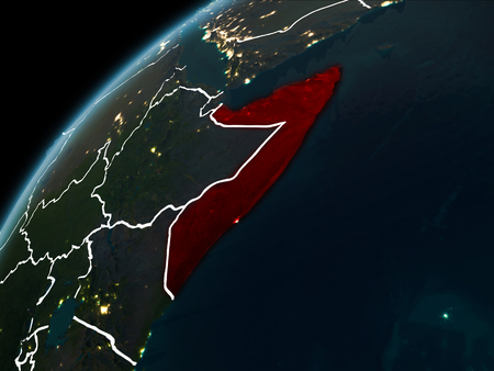 Somalia in red on planet Earth at night with visible borderlines and city lights. 3D illustration. Stock Photo