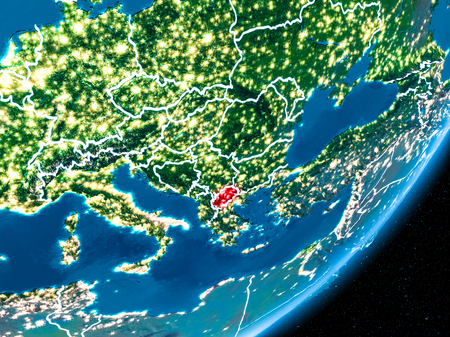 Macedonia in red on planet Earth at night with visible borderlines and city lights. 3D illustration.