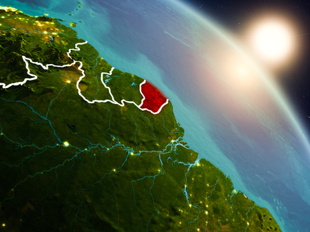 Sunset above French Guiana from space on planet Earth with visible country borders. 3D illustration.