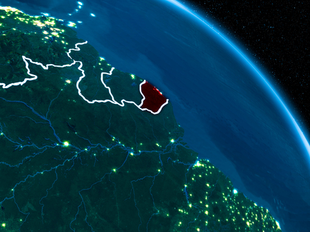 Satellite view of French Guiana highlighted in red on planet Earth at night with borderlines and city lights. 3D illustration. Stock Photo