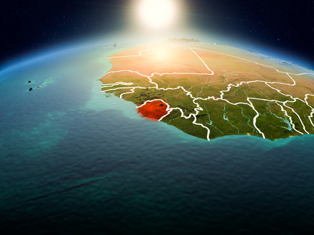 Sunrise above Sierra Leone highlighted in red on model of planet Earth in space with visible country borders. 3D illustration.