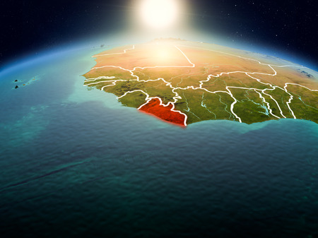 Sunrise above Liberia highlighted in red on model of planet Earth in space with visible country borders. 3D illustration. Фото со стока