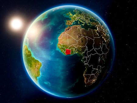 Sunset above Ivory Coast highlighted in red on planet Earth with visible country borders. 3D illustration. Stock Photo