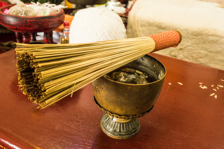 Thai holy water in the bowl with wood stick for splash water.