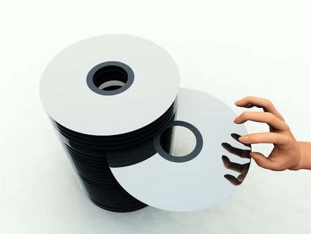 An image of what could be some DVDs or CDs. With a hand taking one from the pile Stock Photo