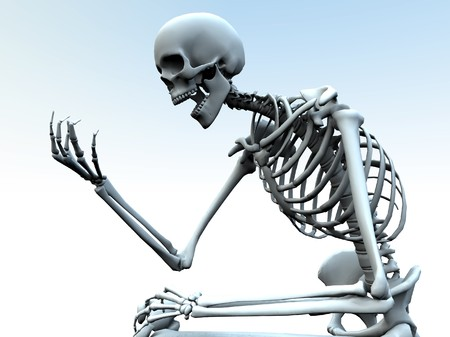 A skeleton looking at its own bony hand. Stock Photo