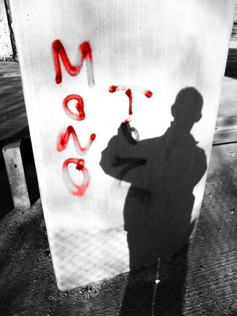 shadowy: Vandal at work spraying graffiti on a pillar. Stock Photo