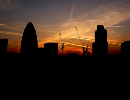 Silhouette of the skyline of London against a sunset sky.  photo