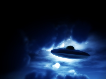 extra terrestrial: A view of a UFO amongst some moonlit clouds.