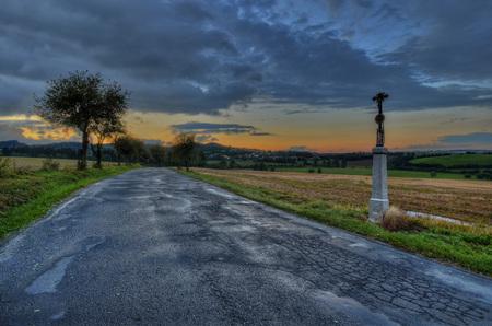 memorial cross: croce commemorativa a strada di campagna al tramonto Archivio Fotografico