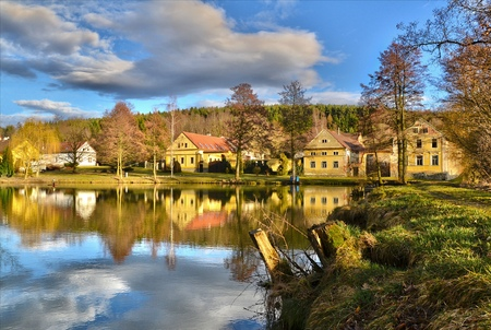 tranquil scene from a small village with a fishing pond photo