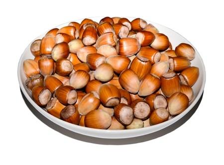 resonator: bowl full of hazelnuts isolated on white