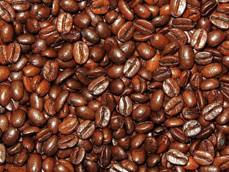 Fresh roasted coffee beans background, texture. Arabica bean wallpaper, close-up.