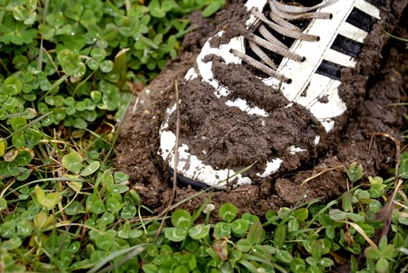 Old shoe stuck in mud Stock Photo