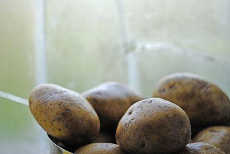 Potatoes in saucepan in front of window Stock Photo