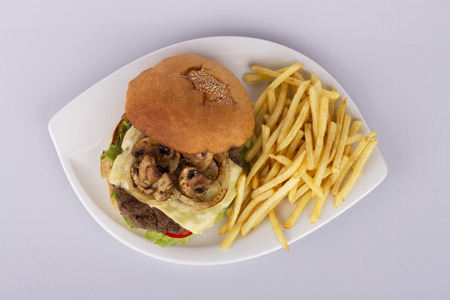 sandwitch: Top view of burger sandwich with cheese, onions, tomatoes and mushrooms with a side dish of french fries Stock Photo