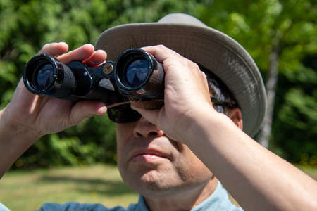 A closeup shot of a man using a pair of binoculars to look at something in the sky. Vancouver BC Canada