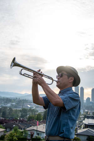 A man playing the trumpet on a hill as the sun rises.   Vancouver BC Canada