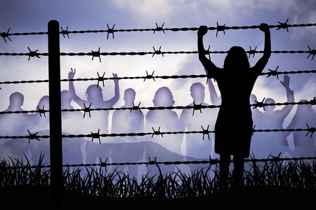 people are captured behind barbed wire Stock Photo
