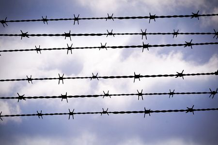 political prisoner: people are captured behind barbed wire Stock Photo