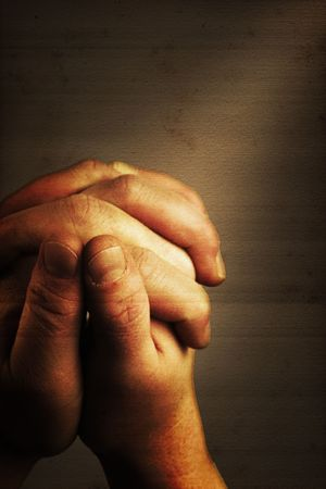 Prayers hands and sunbeam on old nostalgic background Stock Photo