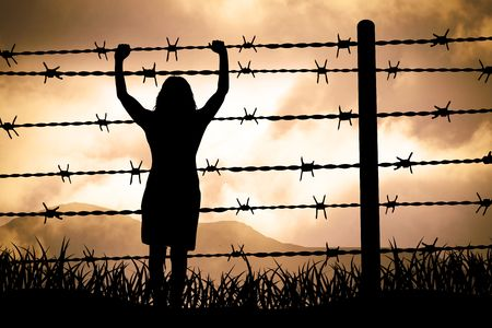 people are captured behind barbed wire photo