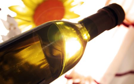 The sun is shining behind a bottle of wine photo