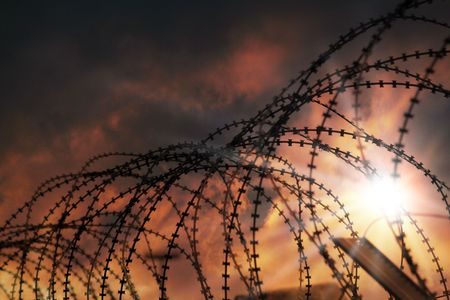 the barbed wire with clouds and sunblades Stock Photo - 5100605