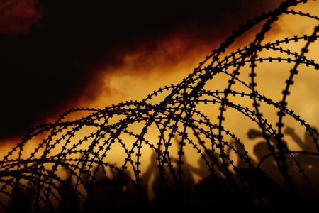 war refugee: the barbed wire with clouds and light Stock Photo