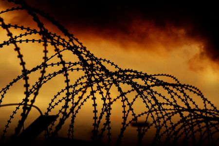 communistic: the barbed wire with clouds and light Stock Photo
