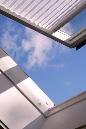 opened roof window with shutter and clouds photo