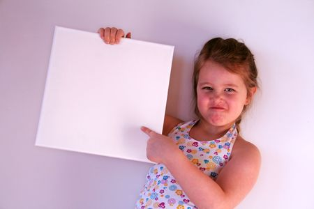 A girl is holding a white frame in her hands
