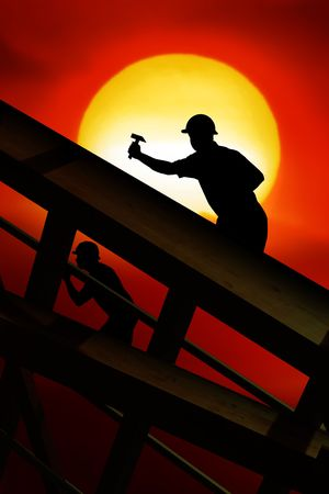 hummer: two workers on a roof top with sunset Stock Photo