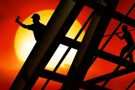 house robes: two workers on a roof top with sunset Stock Photo