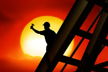 roofer: two workers on a roof top with sunset Stock Photo