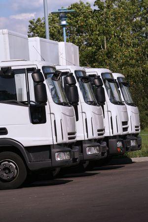 vier vrachtwagens van een transport bedrijf in een rij